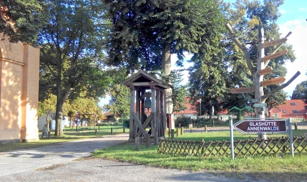 Bushaltestelle Annenwalde, links die Kirche, dahinter die Glashütte
